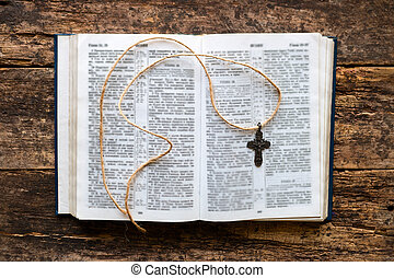 Open bible and cross on a wooden background
