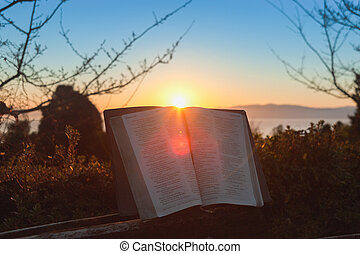 Open bible at sunrise with flare in Fuji city, Japan. Background with sea, mountain and blue sky