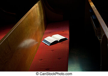 Open bible on top of a padded church pew. Narrow band of light on book, but rest of church is dark.