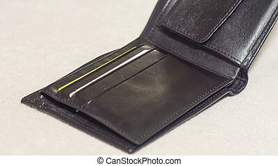 Open black leather wallet on a light background