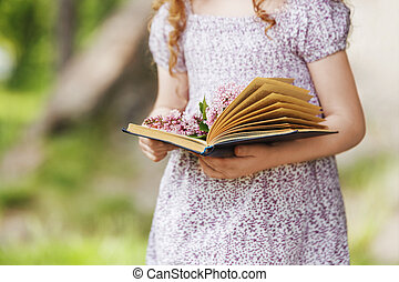 Open book and a bouquet of lilac in the hands of a child.