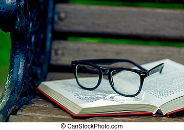 open book and black stylish glasses on a wooden bench in the park, close-up photo