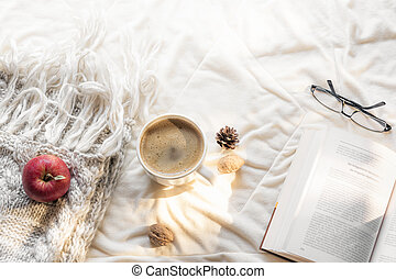 Open book and hot drink on sunny day