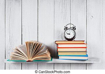 Open book, multi-coloured books and alarm clock. - The open...