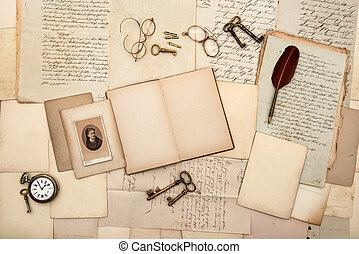 open book, old letters, post cards, glasses, keys, clock