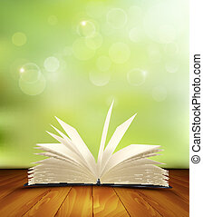 Open book on a wooden floor in front of a green background....