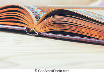open book on the wooden table with copy space, selective focus and shallow depth of field