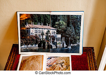 Open book with a photo of a beautiful building stands on the table against the background of the wall