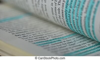 Open book with English text close up. White pages turn in slow motion. Some lines are highlighted in blue, and some in pink, to quickly find the main points. Education concept.
