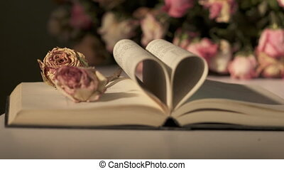 Open book with pages forming heart shape and withered rose flowers