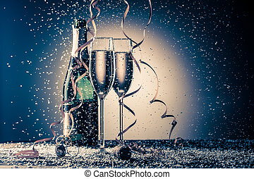 Open bottle of champagne and two filled glasses, festive composi