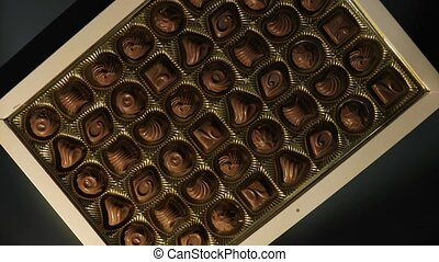 Box of chocolate bonbon candieson a table spinning, camera zooming in