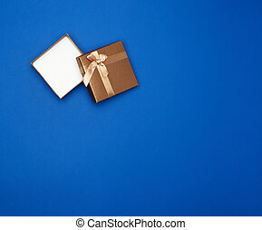 open brown square cardboard empty box, item lies on a blue classic background color