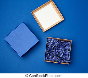 open brown square cardboard empty box, item lies on a blue classic background