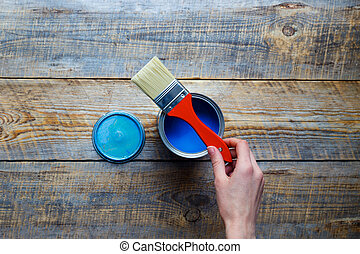 open can blue paint with hand on wooden background