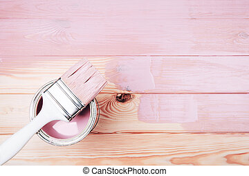 Open can of pink paint with white brush on painting wooden board.