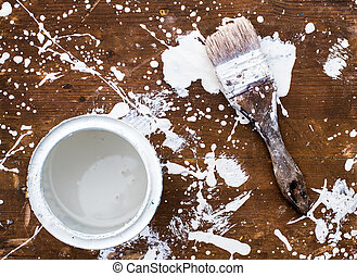 Open can of white paint with brush on wooden background