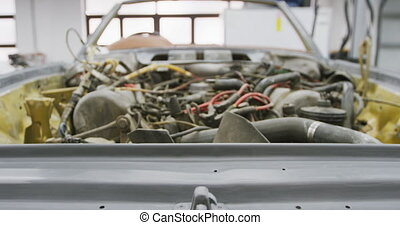 Open car engine standing in a township workshop being prepared to be repaired
