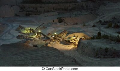 Open cast mine at night with concentrating mill and...