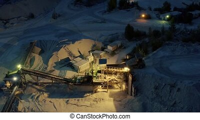 Open cast mine at night with concentrating mill and back-...