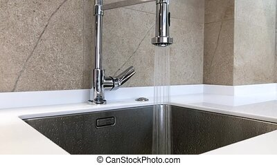 Open chrome faucet washbasin in modern kitchen