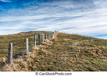 open country landscape with grassy meadow and rime and ice and old wooden fence in the middle under an expansive sky