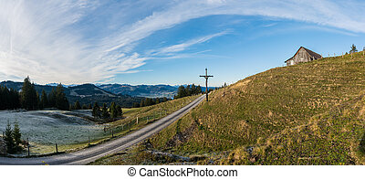 open country landscape with grassy meadow and road and rime and ice and old wooden cross in the middle under an expansive sky and a wooden hut up on the hill