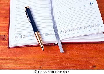 Open diary with pen lying on a wooden table