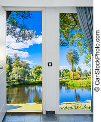 open door with a view of green meadow