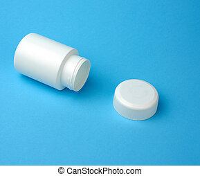 open empty white plastic container for pills lies on a blue background