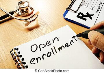 Open enrollment written on a note. - Open enrollment written...