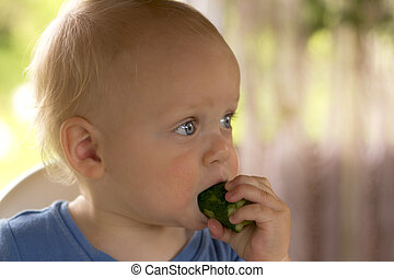 Open-eyed blondy toddler eating a cucumber and kees calm.