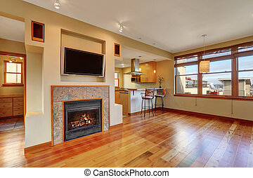 Open floor plan. View of fireplace in the living room with hardwood floor.