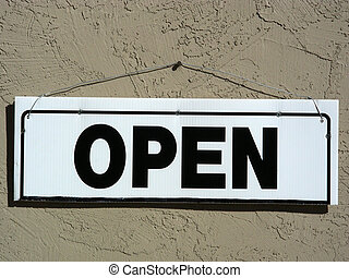 Open for Business - Open sign hanging by a nail on an adobe...