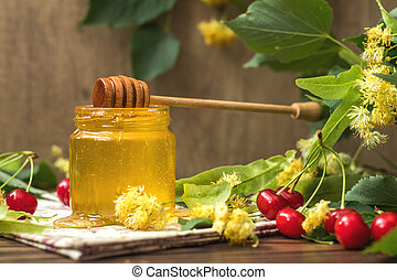 Open glass jar of liquid honey and honey dipper, bunch of...
