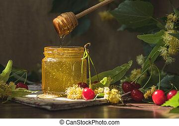 Open glass jar of liquid honey and honey dipper, bunch of...