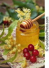 Open glass jar of liquid honey, apple and honey dipper, bunch of linden flowers