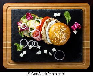 Open hamburger lies on the slate tile.