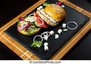 Open hamburger lies on the slate tile