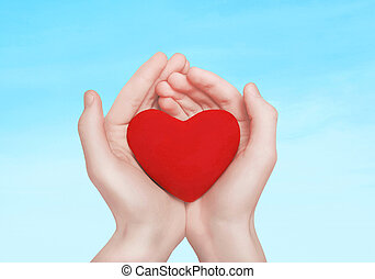 Open hands holding showing red heart over blue sky background