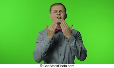 Happy open-hearted handsome man sending air fly kisses, sharing love positive emotions to everyone and smiling carefree, generosity kindness concept. Portrait of guy posing on chroma key background