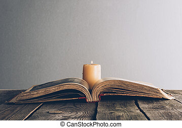 open holy bible with candle on wooden table