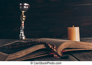 open holy bible with rosary, chalice and candle on wooden table, Holy Communion