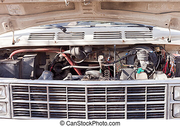 Open hood of old van shows engine and front grille
