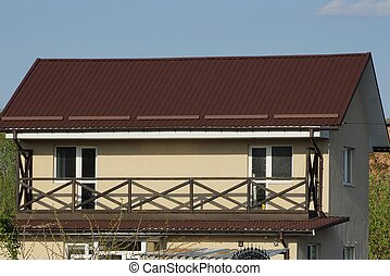 open long brown wooden balcony on the wall of a private house under a tiled roof