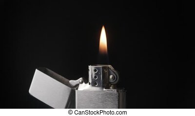 Open metal lighter zippo with flame on black background -...