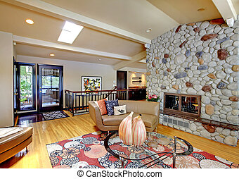 Open modern luxury home interior living room and stone fireplace.