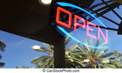 Open neon sign glowing in the dark. Vivid retro styled text at entrance on glass window. Colorful electric banner selective focus close up. Light bulbs radiance at night. Shiny illuminated lettering