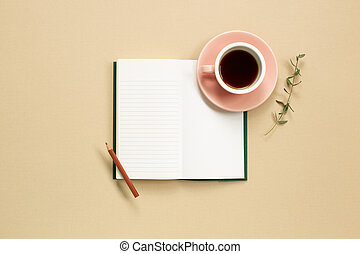Open note book with cup of coffee on beige background. flat lay, top view, copy space