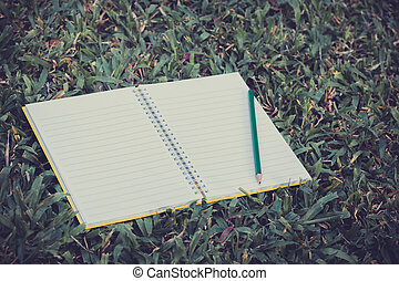 open notebook and pencil on grass field in park with vintage style